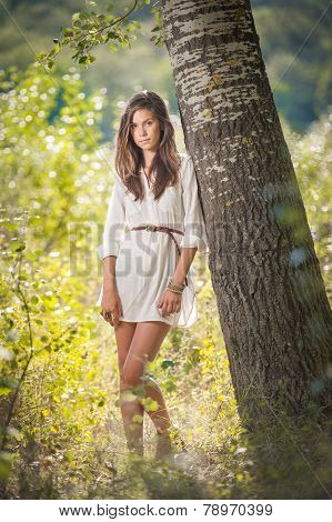 Attractive young woman in white short dress posing near a tree in a sunny summer day. Beautiful girl