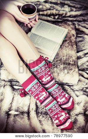 Female Legs In Christmas Socks With A Book And A Cup Of Coffee