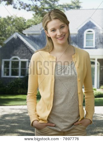 Woman Smiling at Camera Outside Of Her Home