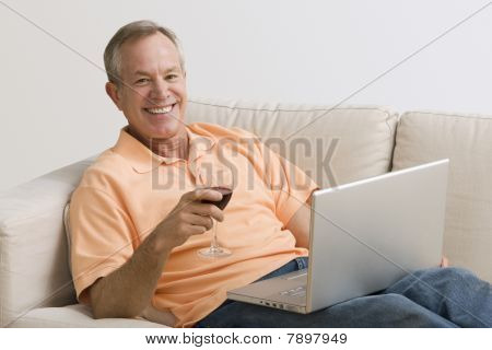 Man Using Laptop and Drinking Wine