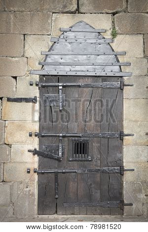 an ancient wooden door with several protection bars
