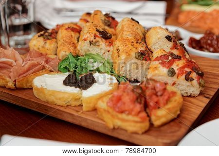 Italian appetizers on wooden plank, close-up