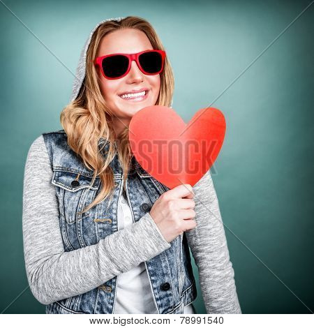 Funky girl in love, isolated on blue background, holding in hands red paper heart, romantic gift on Valentine day, adolescence affection concept