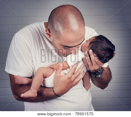 Portrait of gentle father kissing his little newborn daughter, enjoying  at home, happy fatherhood concept