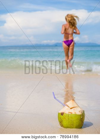 Woman on the tropical beach with young coconut fresh drink selective focus