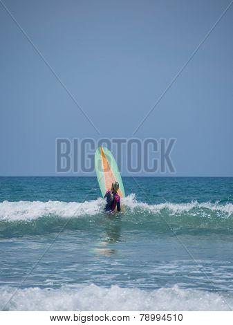 Beautiful young woman surfing in Kuta Bali