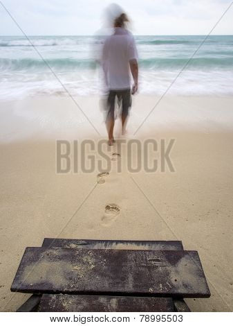 Back view of a man walking and leaving footprints on the sand of a beach - Motion blur focused on the stairs