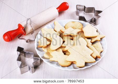 Gingerbread cookies on plate with copper cookie cutter and rolling pin on wooden table background