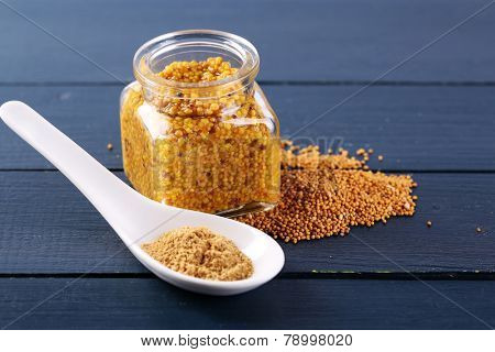 Mustard in glass jar and mustard powder in spoon on wooden background