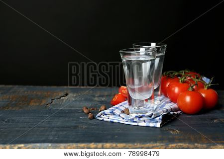 Glasses of ouzo and tomatoes on wooden table, on grey background