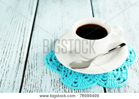 Cup of coffee on lace doily on color wooden background