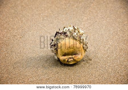 Creepy doll head on beach