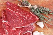 pic of flesh  - fresh raw beef meat fillet flesh with peppercorn and thyme ready to grill on wood figured old style board isolated over white background - JPG