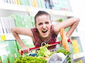 stock photo of grocery cart  - Angry woman pushing a full shopping cart at store with shelves on background - JPG