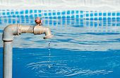 pic of dripping  - faucet dripping in a blue pool on a sunny day - JPG