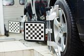 stock photo of machine  - Automobile car wheels with computerized alignment machine clamp - JPG