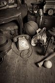 stock photo of attic  - Group of vintage assorted items on attic hardwood floor with vintage wallpaper background - JPG