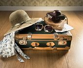 stock photo of leaving  - Vintage traveler suitcase with sunglasses straw hat old camera and maps - JPG