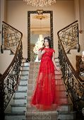 image of wearing dress  - The beautiful girl in a long red dress posing in a vintage scene - JPG