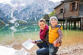stock photo of south tyrol  - Happy mother and baby with map on lake braies in south tyrol italy - JPG