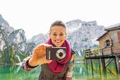 picture of south tyrol  - Portrait of happy young woman taking photo on lake braies in south tyrol italy - JPG