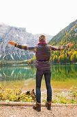 image of south tyrol  - Full length portrait of young woman rejoicing while on lake braies in south tyrol italy - JPG