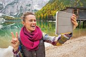 image of south tyrol  - Happy young woman making selfie with tablet pc while on lake braies in south tyrol italy - JPG