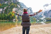 picture of south tyrol  - Young woman on lake braies in south tyrol italy rejoicing - JPG