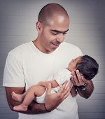 pic of father time  - Portrait of handsome father holding on hands cute little baby - JPG