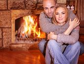 foto of chalet  - Portrait of gentle couple sitting near fireplace at home - JPG
