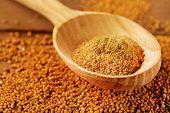 image of mustard seeds  - Mustard powder in wooden spoon on mustard seeds - JPG