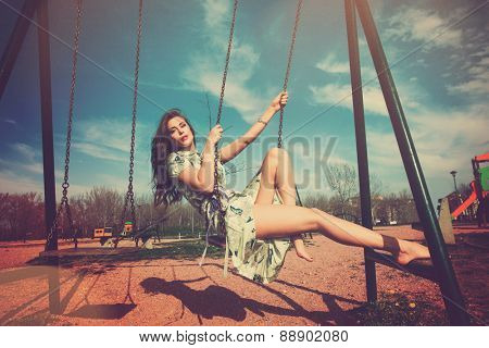 barefoot young woman sit on swing in summer dress in playing park , full body shot, retro colors, color leek texture added