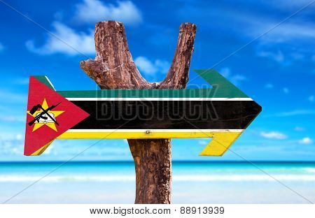 Mozambique Flag wooden sign with beach background