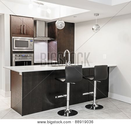 Modern luxury kitchen interior with dark wood cabinets, island counter, bar stools and stainless steel appliances