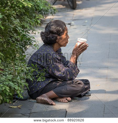 Thai Old Beggar Woman Waits For Alms On A Street
