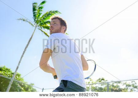 Male tennis player finishing serve playing outdoor. Man serve for game during outside tennis game. Fit male athlete living healthy fitness sport lifestyle. Young Caucasian model in his 20s.