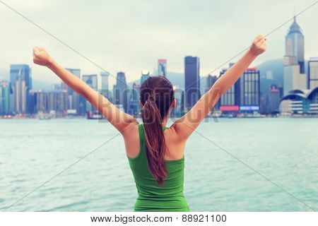 Happy woman success cheering by Hong Kong skyline with arms raised up outstretched. Successful winner celebrating cheerful on Tsim Sha Tsui Promenade and Avenue of Stars in Victoria Harbour, Kowloon.