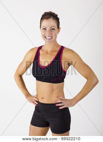 Portrait of a beautiful strong muscular woman looking at the camera. Serious Female body builder with hands on her hips