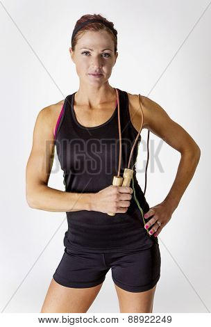 beautiful strong muscular woman looking at the camera. Serious Female body builder with jump rope isolated on a white background