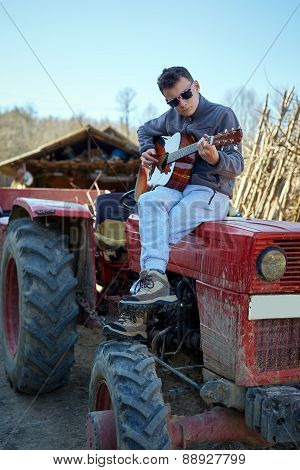 Teenage Boy Playing Guitar On A Tractor