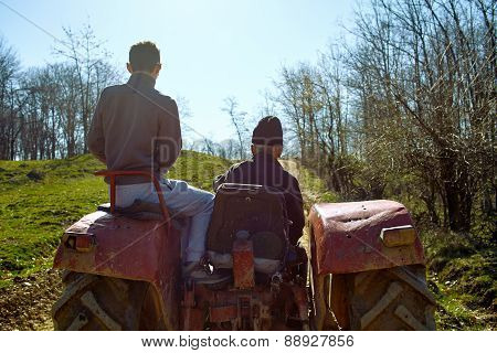 Grandfather And His Grandson Driving A Tractor At Sunset