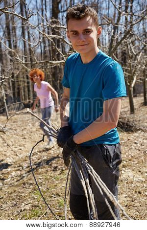 Teenager Boy And His Mother Spring Cleaning The Orchard