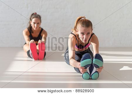 Two young women stretching reaching  with hands to toes seated forward bend warm up at gym fitness,