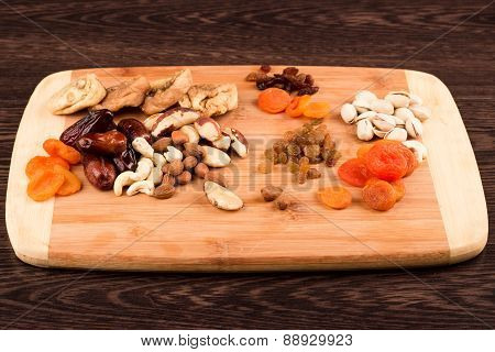 Snacks Of Nuts And Dried Fruits On A Wooden Surface