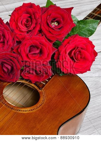 Bouquet Of Red Roses On Top Of Classical Guitar