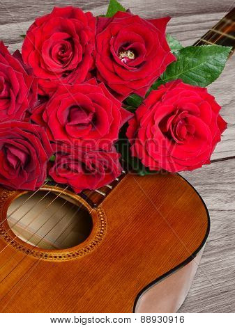 Bouquet Of Red Roses On Top Of Acoustic Guitar