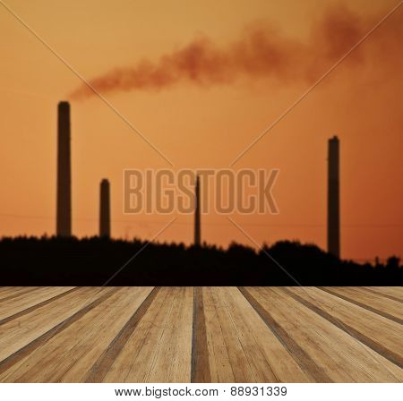 Industrial Chimney Stacks In Natural Landscape With Wooden Planks Floor