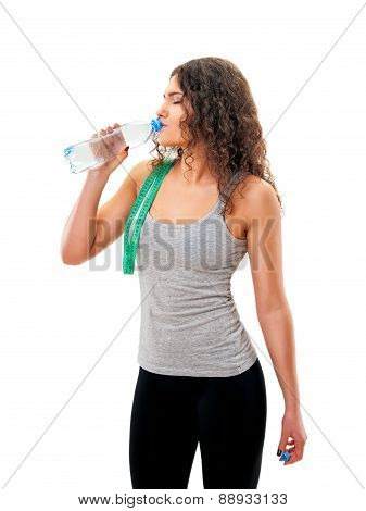 girl with measuring tape is drinking water from a bottle