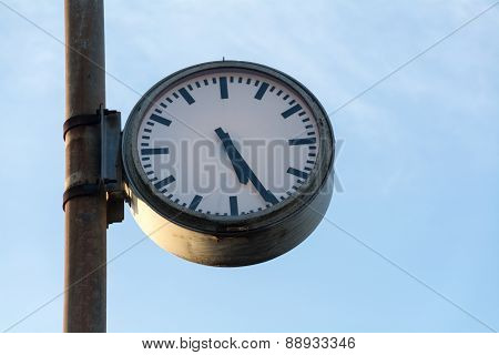Big Old Clock At A Rusty Pole Against The Blue Sky