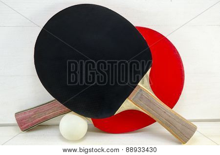 Two Table Tennis Rackets And A Ball